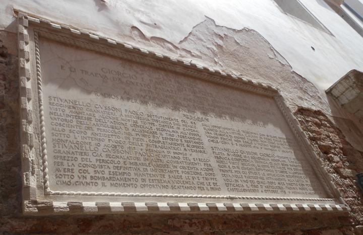 Lapide di forma rettangolare con caratteri piombati in lapidario romano; cornice a fascia con motivo decorativo a dentelli alternati all'esterno, e corda in stile gotico veneziano all'interno.