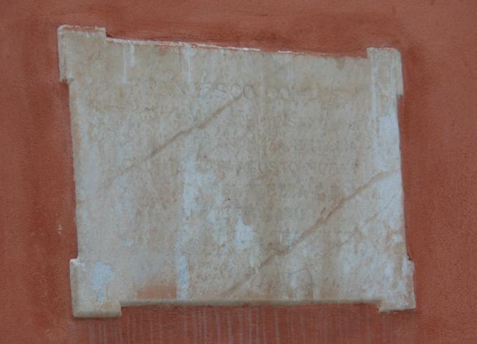 Lapide marmorea dedicata a Francesco Cortesi. Forma rettangolare, tagliata sui lati da quattro segmenti; iscrizione al centro.